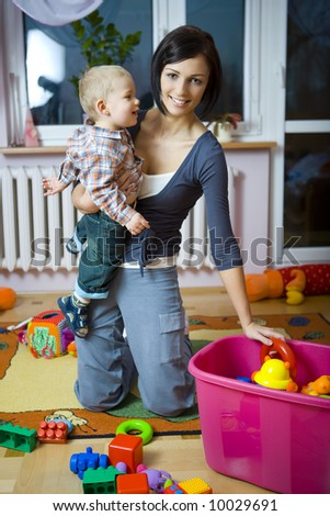 Young woman with baby boy during plaing. Woman holding baby on hand taking toy from container. Front view. - stock photo