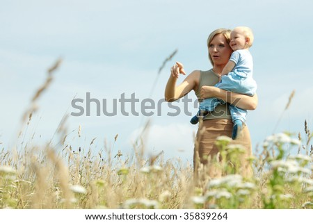 Young woman with baby on her shoulders in a country field of tall grass. - stock photo