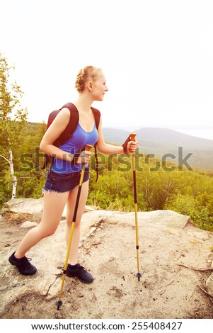 young woman with backpack hiking in the mountains. people outdoors. healthy lifestyle - stock photo