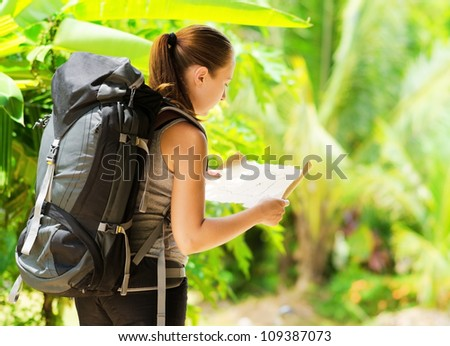 Young woman with backpack in a woods. Hiking at summertime. - stock photo