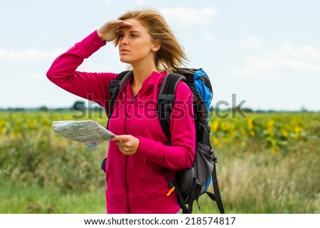 Young woman with backpack  is holding a map and looking  which way to go,Where am I? - stock photo