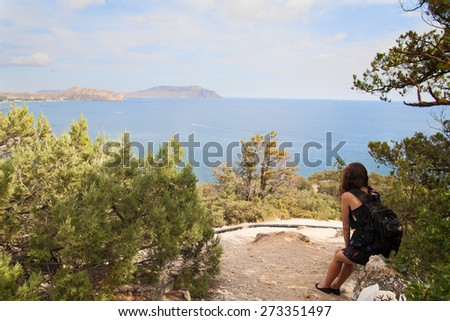 Young Woman with backpack relaxing near the sea. - stock photo