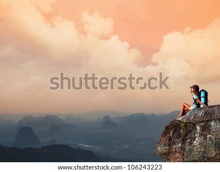 Young woman with backpack sitting on a cliff and looking to a valley - stock photo