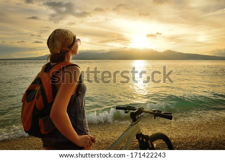 Young woman with backpack standing on the shore near his bike and enjoying the sunset over the sea on the background of the island Negros, Philippines. - stock photo