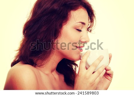 Young woman with beautiful face is having her tea or coffee - stock photo