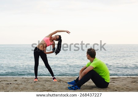 Young woman with beautiful figure doing stretching exercise on the beach, couple working out against the sea at evening time, athletic man taking a break while his girlfriend exercising - stock photo
