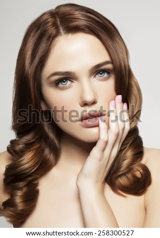 Young woman with beautiful healthy face and hair. Hand on the face - stock photo