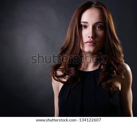 Young woman with beautiful long brown hair posing at studio, looking at camera, face closeup, over black background - stock photo