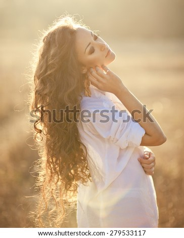 Young woman with beautiful long curly hair posing in a field at sunset. Summer mood - stock photo