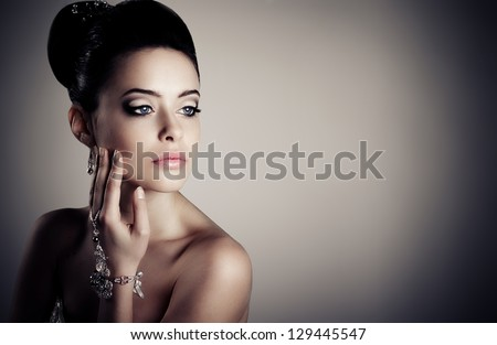 Young woman with beautiful make-up, against a dark background. - stock photo