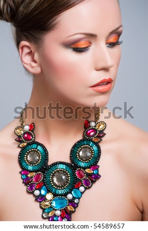 Young woman with beautiful makeup and necklace - stock photo