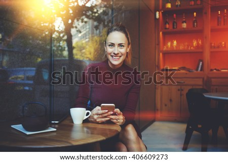 Young woman with beautiful smile posing while sitting with smart phone in modern coffee shop interior, gorgeous cheerful female chatting with her friends via cell telephone during rest in cozy cafe  - stock photo