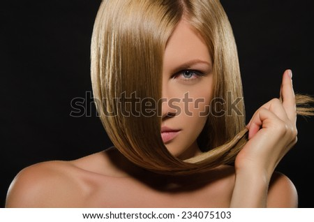 young woman with beautiful straight hair on black background - stock photo