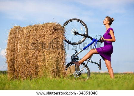 Young woman with bicycle at the field. Freaky concept. - stock photo