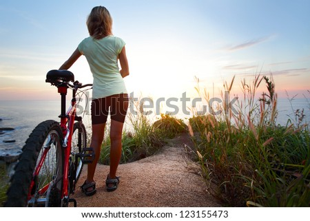 Young woman with bicycle standing on ground and enjoying sunset over sea - stock photo