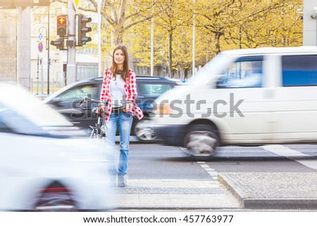 Young woman with bicycle waiting to cross the street at red signal in Berlin. There are blurred cars passing in front of her and behind. Urban lifestyle and travel concepts. - stock photo