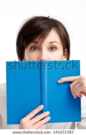 young woman with big blue eyes hiding behind a book, looking to the viewer on white background - stock photo