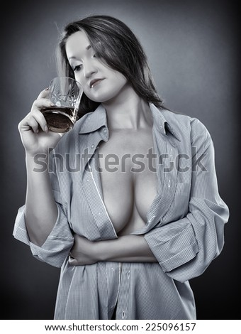 Young woman with big breasts and deep cleavage having a glass of whiskey, toned monochrome - stock photo