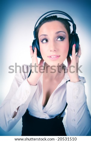 Young woman with big headphones. On soft blue tint. - stock photo