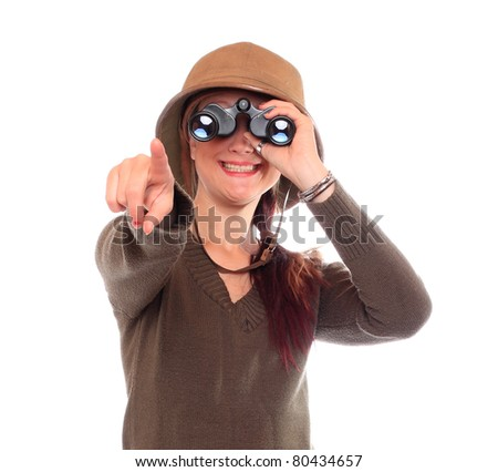 Young woman with binocular dressed in safari suit watching here happy holidays. - stock photo