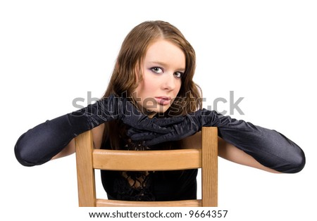 Young woman with black gloves on wooden chair. Isolated on white. - stock photo