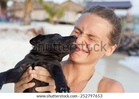 young woman with black puppy in the hands - stock photo