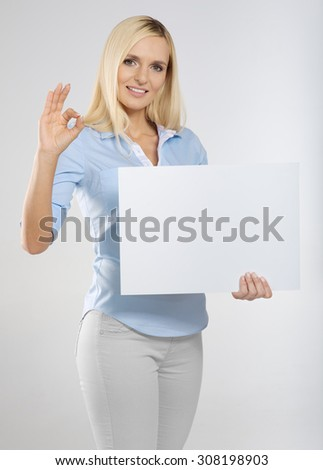 young woman with blank sign board and showing okay gesture - stock photo
