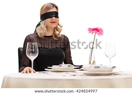 Young woman with blindfold on her eyes sitting at a romantic dinner on a blind date - stock photo