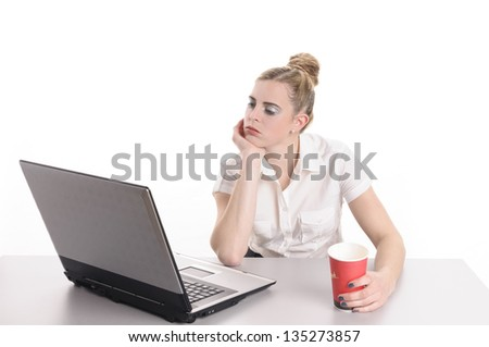Young woman with blond hair wearing a business suit and has bored in the office. She sits far succeeded with a coffee cup in front of her computer keyboard, isolated against white background. - stock photo