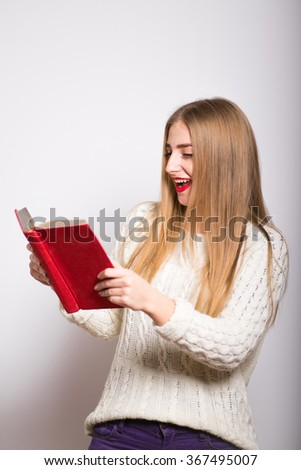 young woman with book. Funny blonde girl reading a book  isolated - stock photo