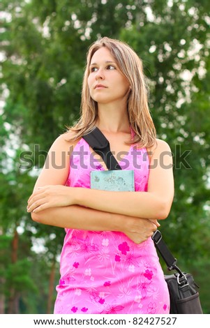 Young woman with book in hand and a bag over his shoulder. Student - stock photo