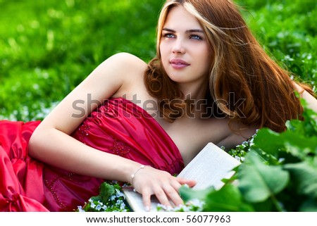 Young woman with book in summer park. - stock photo