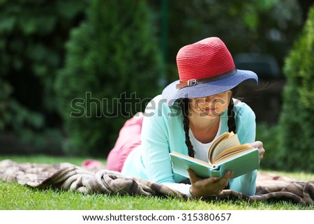 Young woman with book lying on green grass outdoors - stock photo