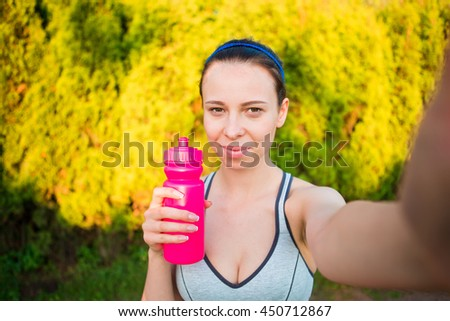 Young woman with bottle of water after running outside. Female fitness model training outside and taking selfie in the park. Healthy wellness fitness lifestyle. - stock photo