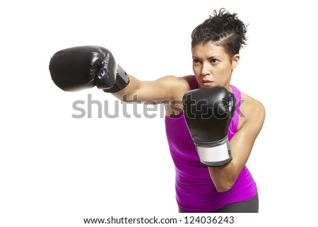 Young woman with boxing gloves throwing a punch in sports outfit - stock photo