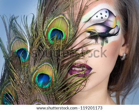 young woman with bright make up and peacock feather - stock photo