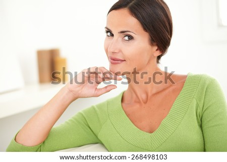 Young woman with brown hair contemplating and looking at camera at indoors - stock photo