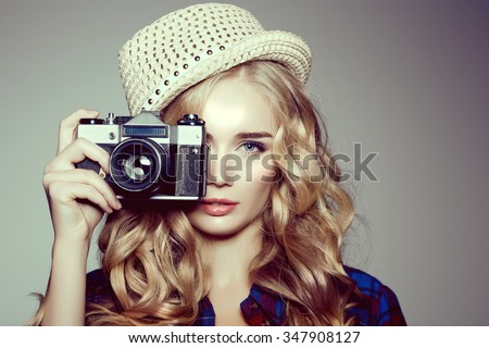 Young woman with camera. Blonde in a plaid shirt. Hipster fashion photographer girl. Young people, youth culture - stock photo