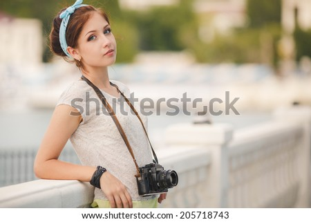 Young woman with camera outdoors portrait. Soft sunny colors. woman with vintage retro camera having fun playful laughing - stock photo