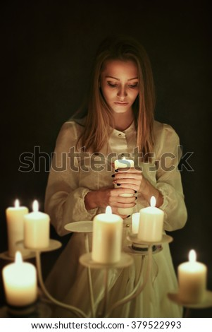 Young woman with candle in hand . Gothic and surreal concept - stock photo