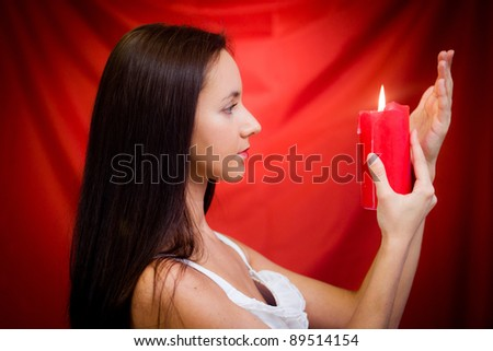 Young woman with candle in studio against red background - stock photo