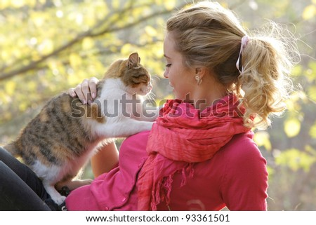 young woman with cat outdoors - stock photo