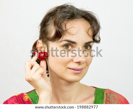 Young woman with cherry at her ear - stock photo