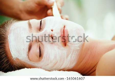 Young woman with clay facial mask - stock photo