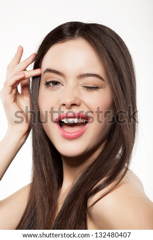 Young woman with clean fresh skin and long hair shows emotion, on white background - stock photo