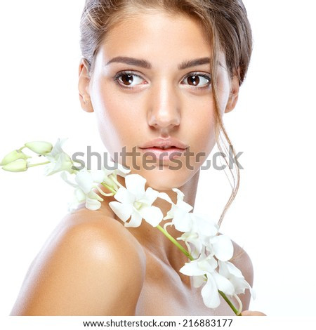 Young woman with clear face natural make up her hair up with a white flower on a light isolated background - stock photo