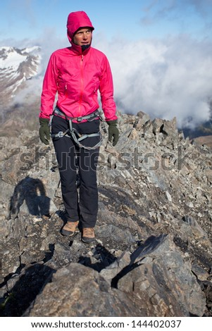 Young woman with climbing harness in alpine scenery - stock photo