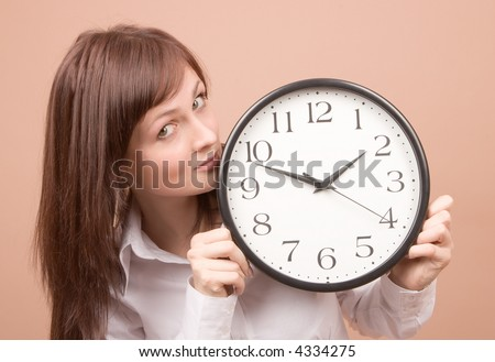 Young woman with clock isolated on beige background - stock photo