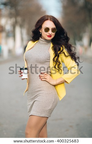 Young Woman with Coffee Cup on the Phone Out in the City - Woman smiling and talking on her phone holding a cup of coffee out in the city. Stylish girl posing at the camera, mirror sunglasses yellow - stock photo