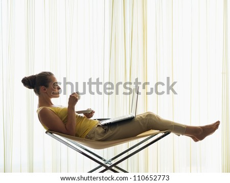 Young woman with coffee cup using laptop at home - stock photo
